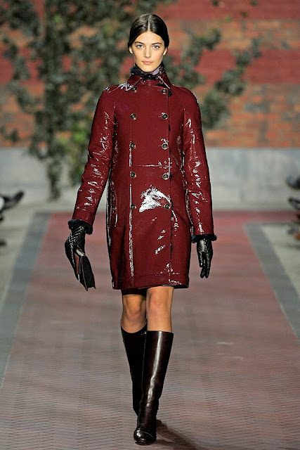 model from tommy hilfiger's fall 2012 runway show wearing an oxblood patent leather pea coat with burgundy flat knee high boots