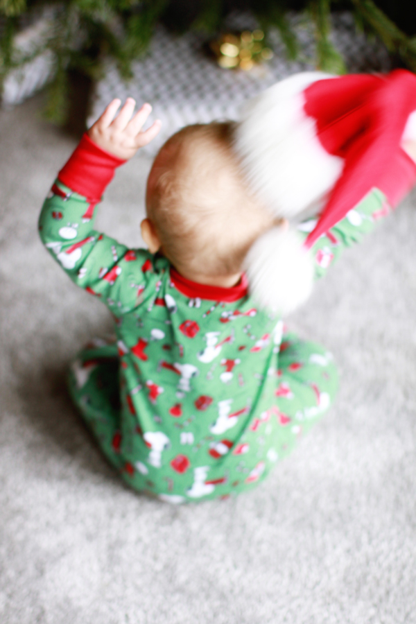 Baby in Christmas jammies & a Santa hat