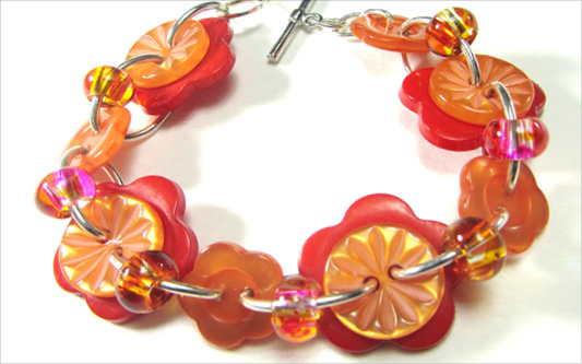 Cute orange bracelet has big flower buttons, carved buttons and glass beads