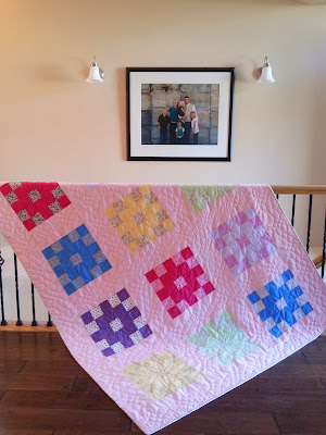 a patchwork quilt with a pink background and lots of bright colors