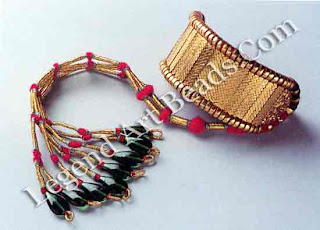 Narrow interlocking vertical gold units set with diamond chips are joined with a thick rope of cotton threads on either side, ending in an elaborate tassel of gold threads and glass beads.