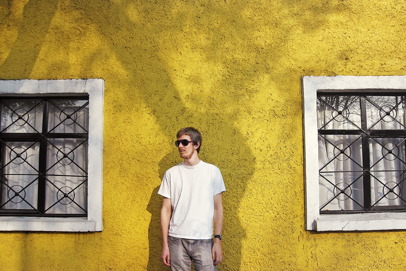 Standing against a bright yellow wall in Coyoacan in Mexico City