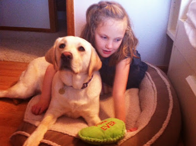 "Hallie lies in Widget's bed with her arm around the adorable yellow Lab (a green plush toy that says ""FOREVER"" is next to them)."
