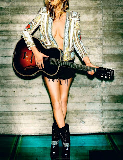 Kate Moss in short shorts holding a guitar