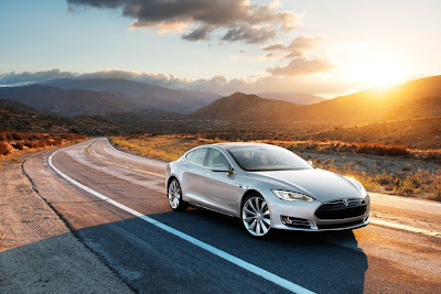Tesla Model S on desert road with sunset