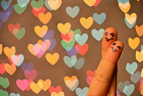 Two crossed fingers, with a smiley face drawn on both in front of a background of love hearts.