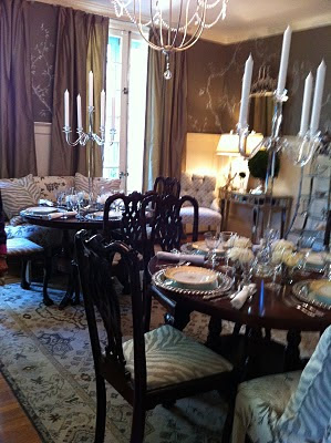 dining room with tables set with plates and large silver candlesticks with 5 white candles in each and dark brown drapes on the two windows