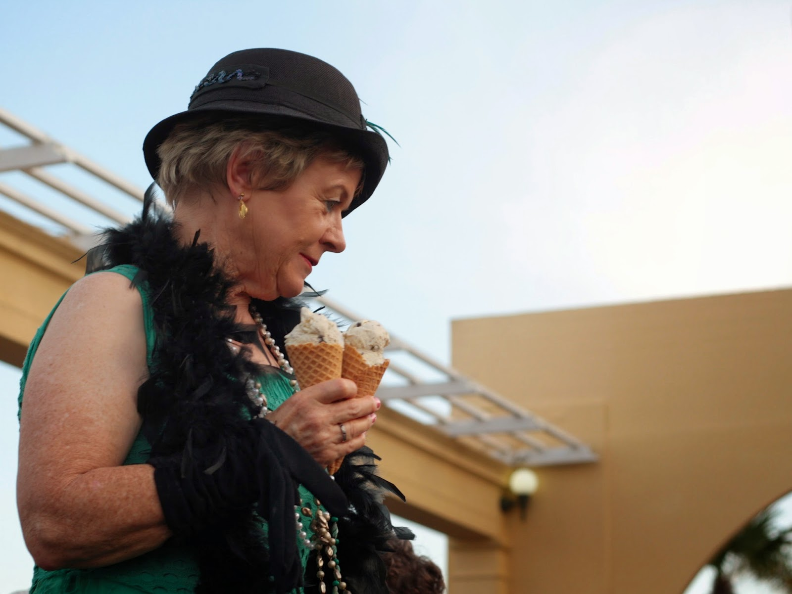 An older woman wearing a cloche hat and a feather boa carries ice creams.