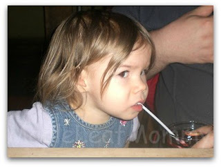 Toddler having a drink from breakable glassware while dining out.