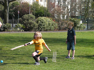 girl in football kit playing cricket