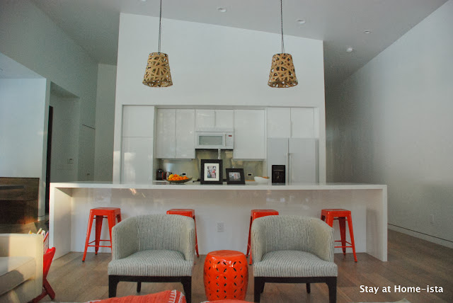 Modern Ikea kitchen in all white modern house accented with orange stools and textured pendants