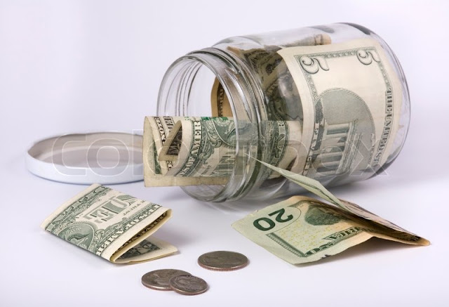 an open glass jar with money
