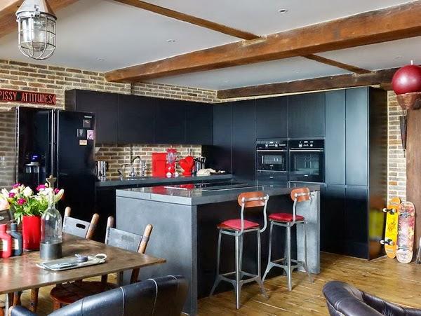 Aranżacja kuchni w lofcie, czarne meble i ściana z cegły