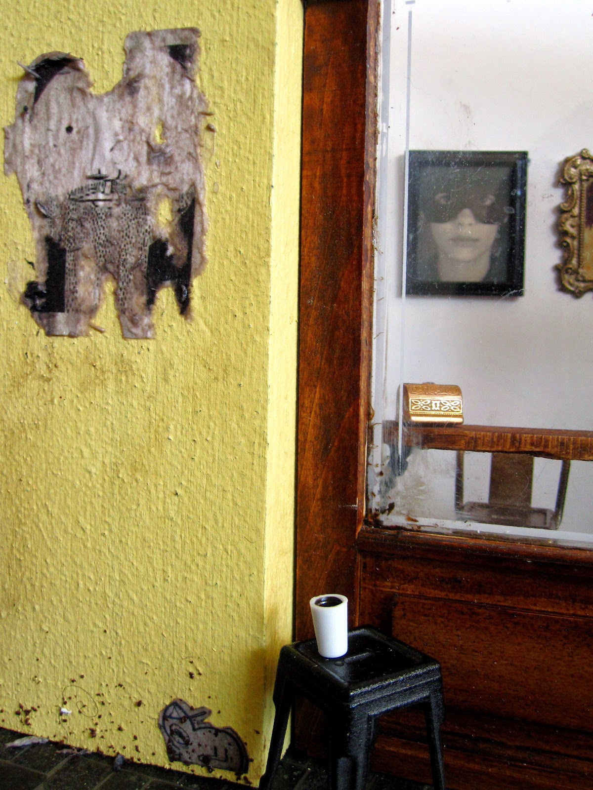 Exterior of a modern dolls' house miniature cafe with paste-ups on the wall.