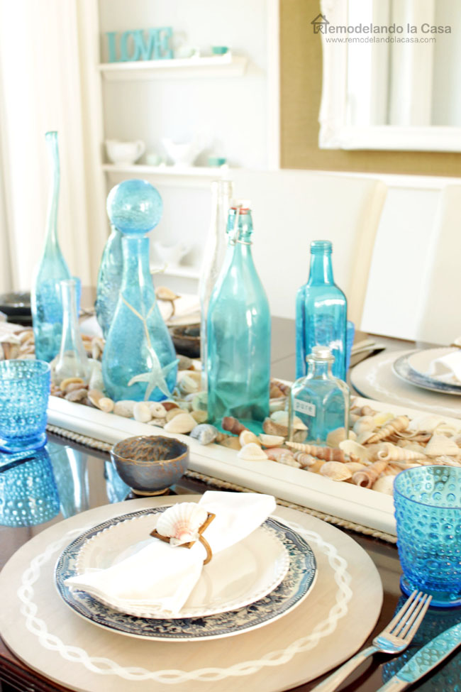tablescape with blue bottles, shell centerpiece and anchor placemats