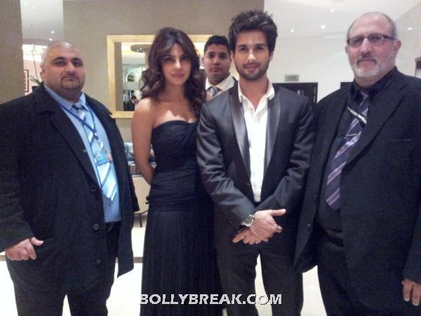 shahid in black suit coat amd priyanka in a black off shoulder dress standing with promoters -  Shahid & Priyanka @London premiere of Teri Meri Kahaani