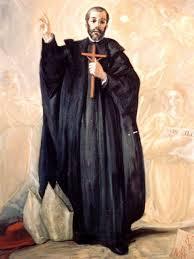 san Juan de Dios vestido de sacerdote con un crucifijo sobrre el pecho y bendiciendo