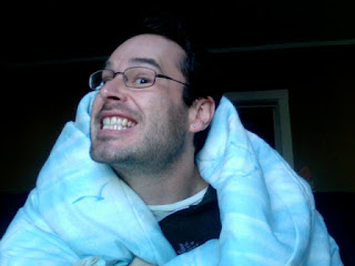 Guy smiling with glasses and a blanket.