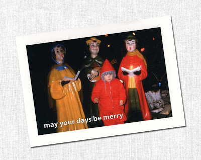 Christmas card of scared boy in front of caroler statues