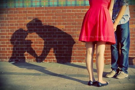 A cute couple kissing on the street forming a nice and awesome shadow of kiss