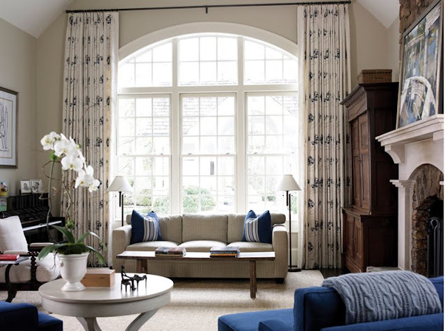 Living room with high ceiling, large arched window with floor length printed drapes, a light grey sofa, blue armchairs, a piano, a wooden chest of drawers and a fireplace with an arched mantel