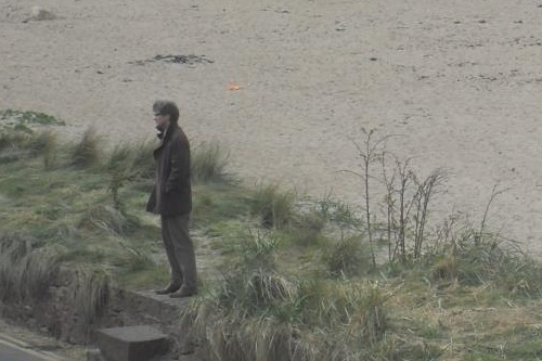 Colin Firth standing on a wall