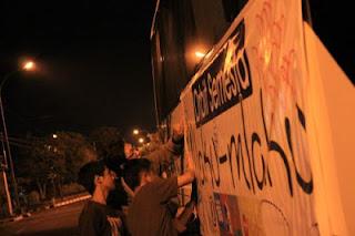 lagi nempel banner di bus