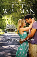 cover of The House that Love Built by Beth Wiseman shows a man and woman holding each other close