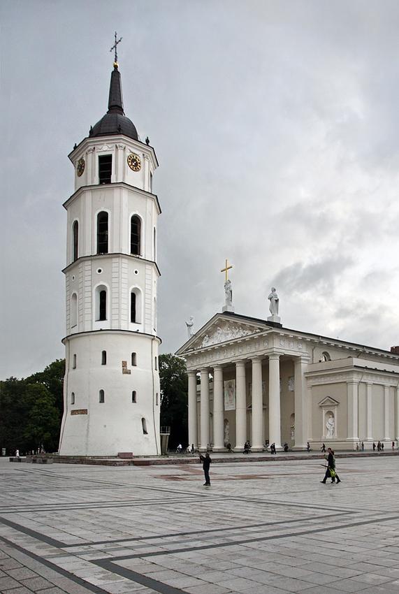 Foto no lardo da catedral. À esquerda a torre e à direita o edifício. Agumas pessoas a passar e uma a tira fotografias. Céu nublado mas luminoso