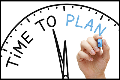 "image of hand writing on a clock: ""time to plan"""