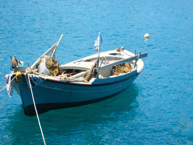 Tiny wooden fishing boat in the ocean on Kefalonia, Greece
