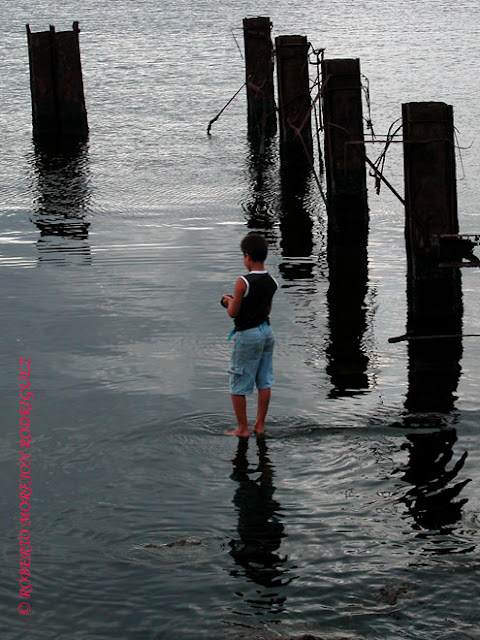 Un niño pescando en el malecón de Regla, un pueblo ubicado en el otro lado de la Bahía de La Habana.