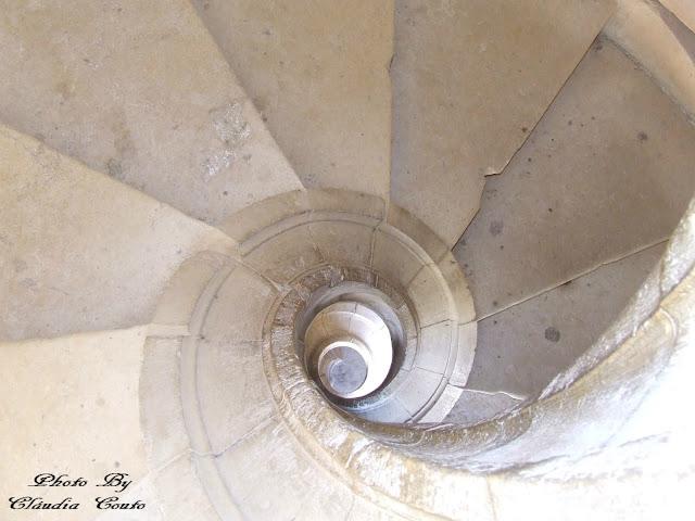 Fotografia de uma escada em caracol, tirada no Convento de Cristo. Um bonito e histórico local onde o frio das pedras se misturam com a elegância da arquitetura.