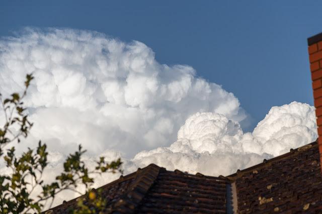 cumulonimbus calvus behind house roof