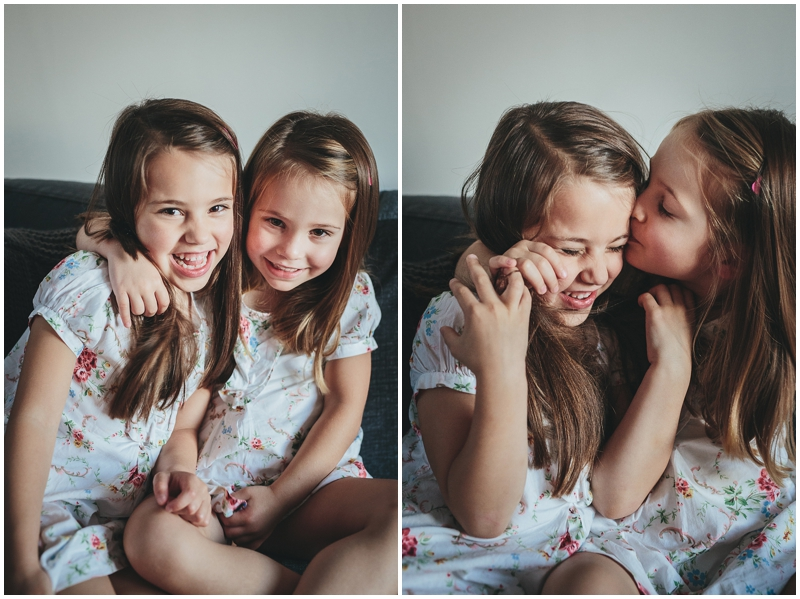Two young sisters cuddling and kissing