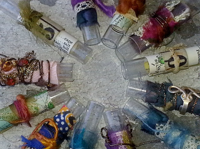 closeup of more fiber arts collage on recycled glass vials