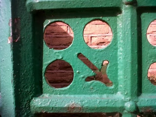 Detail from a green iron fence - three circles and a downward pointing arrow.