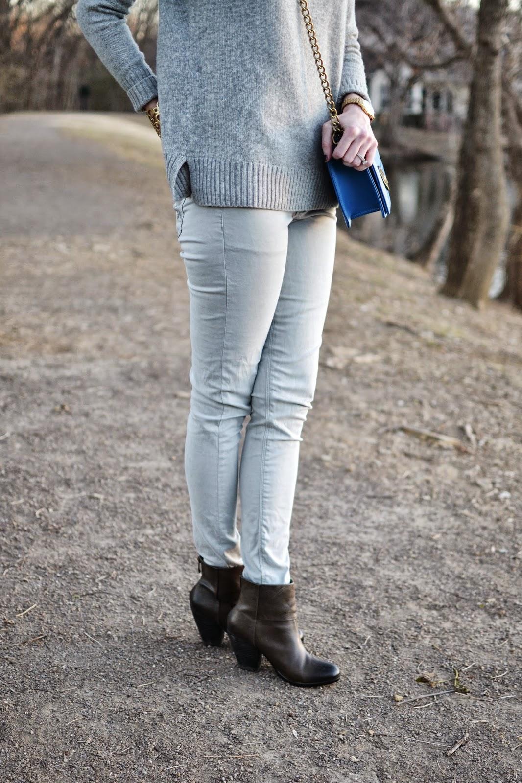 grey turtleneck sweater, grey jeans, grey booties, blue purse, gold jewelry