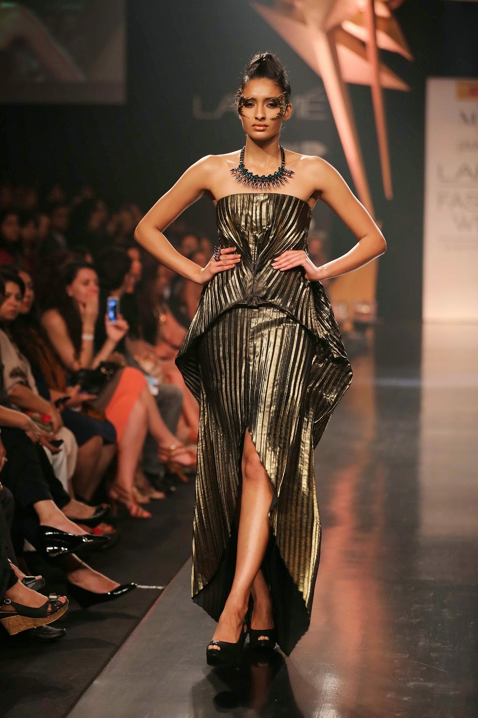 "Antique gold metallic draped one-shoulder gown with an endless trail revealed the futuristic look of the garments; while striking body and jumpsuits, dresses and sari gowns held the attention of the audience. Slim pants were seen under luxurious togas, along with lace gowns and cocktail dresses that were breathtaking in their regal beauty meant for the futuristic Egyptian queens. Mention must be made of the very exotic make-up, the gorgeous gold platform shoes and Mohawk like hair-do that followed the Egyptian theme. When women want to look like Egyptian goddesses then Gaurav Gupta's collection called ""Memphire"" will allow them to compete with beauties of the world and rule the fashion scene."