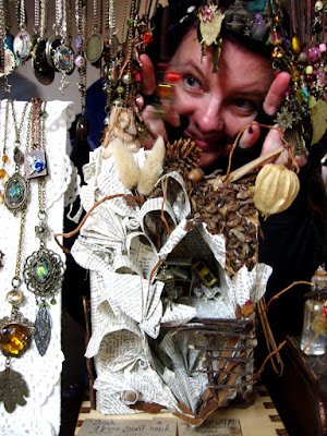 A woman peeks through a display of necklaces on a market stall above a paper house.