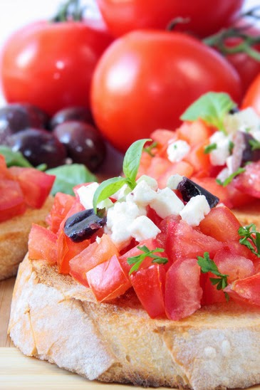 bruschetta with fresh tomatoes and olives in background