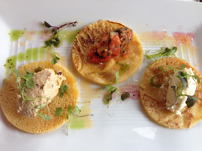 A trio of chickpea crepes were garnished with chili oil and topped separately with field pea hummus, heirloom squash ratatouille, and feta.