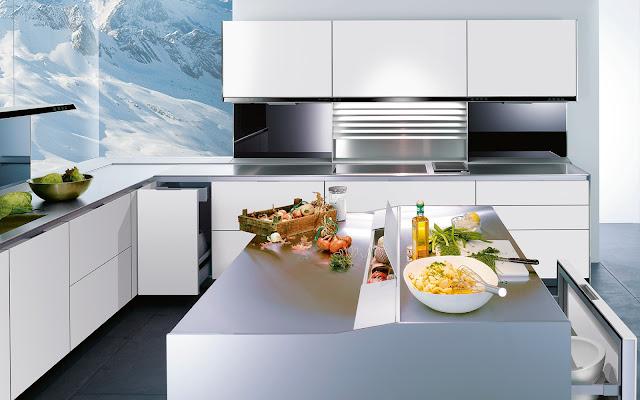 Cuisine design blanche par Siematic. Cette cuisine blanche dispose d'un îlot avec rangement intégré dans sa partie centrale. Les façades sans poignées sont d'une très belle finition, chaque ligne est fine et parfaite.