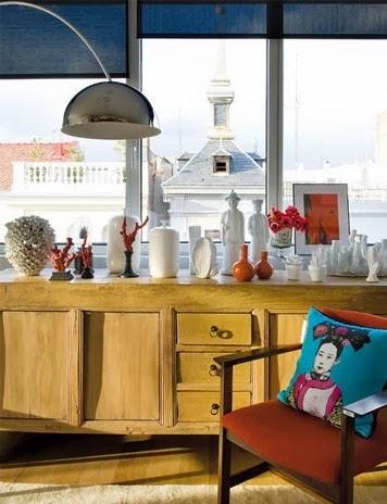 Artystyczne wnętrze, drewniana komoda, oriantalna poducha na designerskim krześle