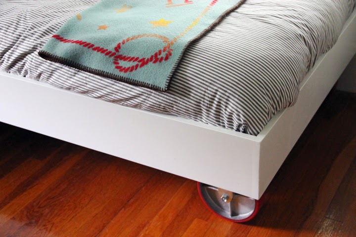 A plastic sheet padded sides and mounted on wheels The