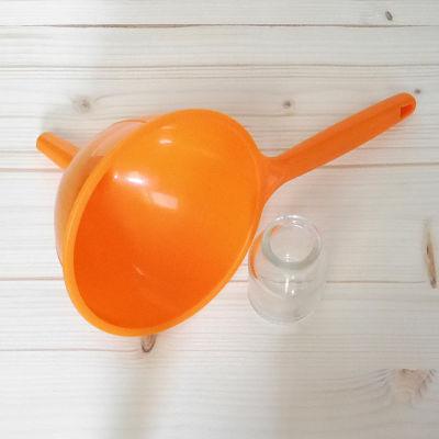 Frasco de cristal vacío y un embudo naranja
