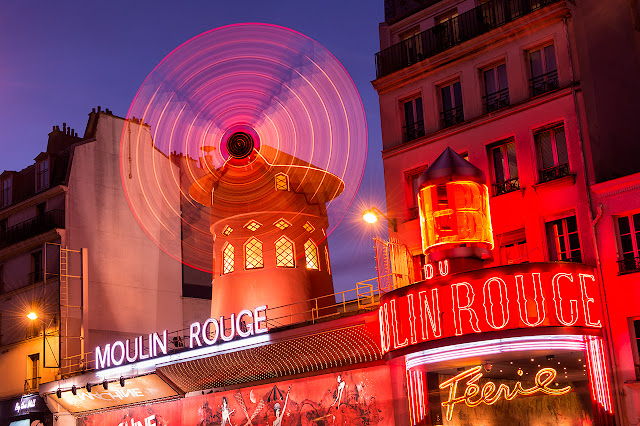 Paris Monmartre district, with spinning wheel and glowing lights of Moulin Rouge.