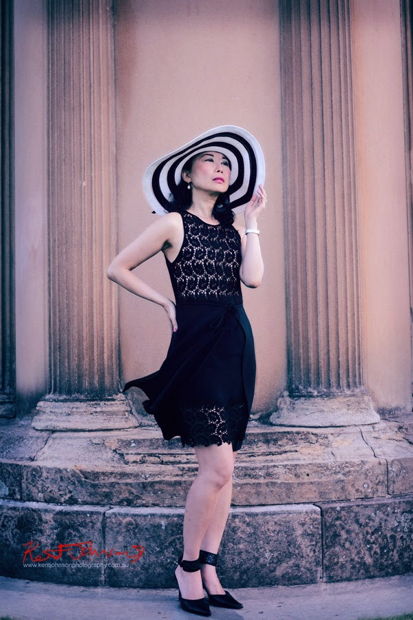 Colour photo, Vivienne standing, Vintage SPAZIO dress, striped hat, shoe with lace cuff, in front of Choragic Monument of Lysicrates, Royal Botanic Gardens, Sydney. Fashion blogger collaboration VivalaViv photographed by Kent Johnson