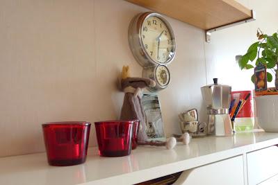 vit vägghylla i kök, med värmeljushållare i rött glas och råttfigur. foto: Reb Dutius