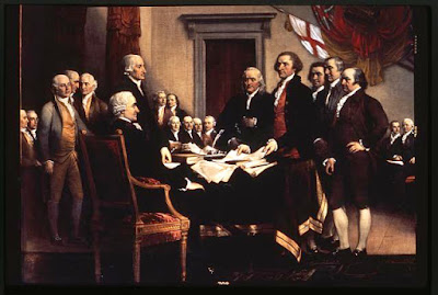American founding fathers, John Adams, Thomas Jefferson, and others standing at a table on which is the Declaration of Independence